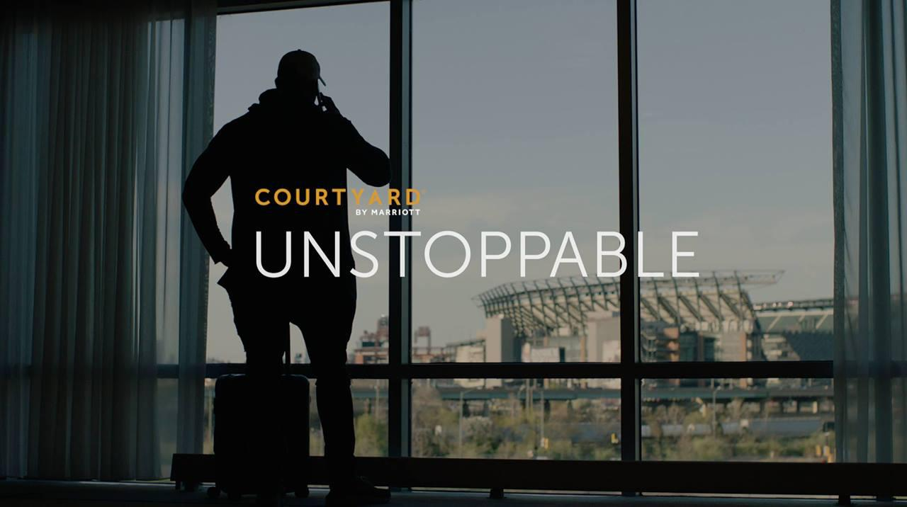 photo of a man in front of a window, with 'courtyard by marriott, unstoppable' text over the top